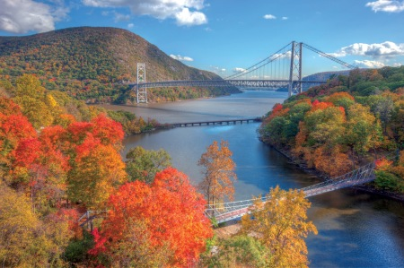 Autumn view of Bear Mountain Bridge with the CSX railroad bridge and the Popolopen Creek Suspension Footbridge in the foreground